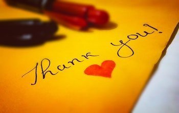 Yellow envelope with thank you written on it and a red heart