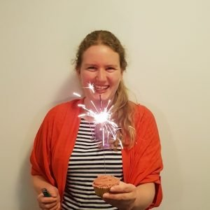 A picture of Jane, a woman with low grade serous ovarian cancer, holding a cup. cake with a sparkler