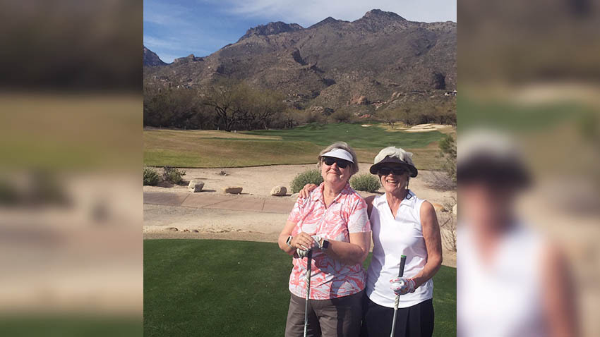 Sharon Ritchie and friend golfing in front of a mountain