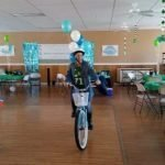Brianna riding a bike inside surrounded by balloons