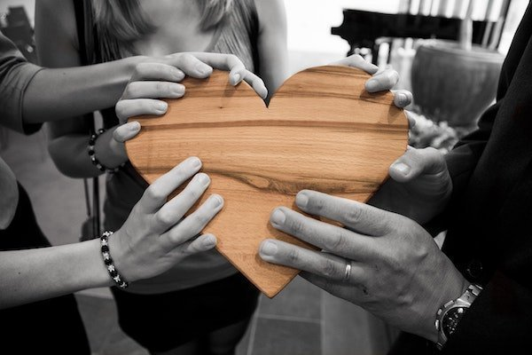 Four hands holding a wooden heart